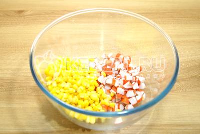 В миске смешать кукурузу и кубиками нарезанные крабовые палочки.