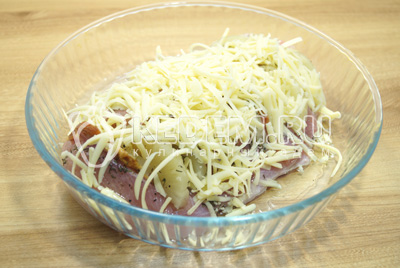 Выложить мясо в форму для запекания и хорошо посыпать тертым сыром.
