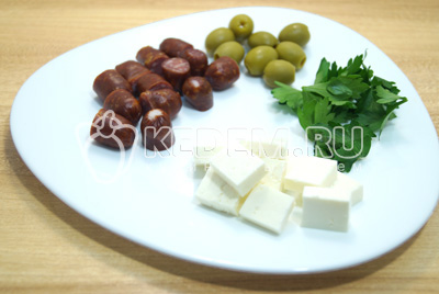 Охотничье колбаски разделить на части. Сыр нарезать кубиками, зелень промыть.