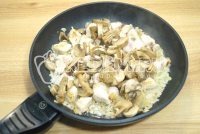 На сковороде с растительным маслом обжарить лук, мясо и четвертками нарезанные грибы. Готовить 3-4 минуты.