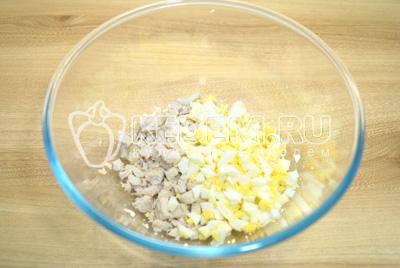 В миску нарезать мелким кубиками куриное филе и яйца.