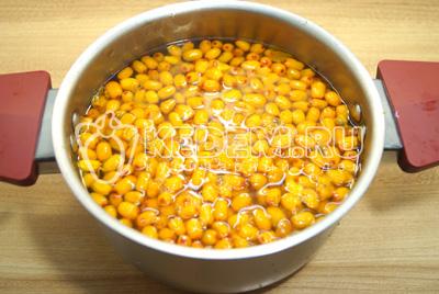 Выложить ягоды в кастрюлю и залить водой.