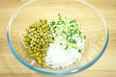 Добавить в миску с рисом горошек и кубиками нарезанный огурец.