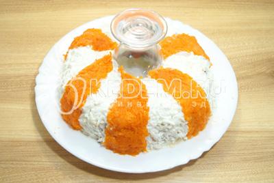 Верхний слой выложит частями из тертой моркови.