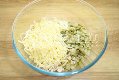 Добавить кубиками нарезанные огурцы и тертый сыр.