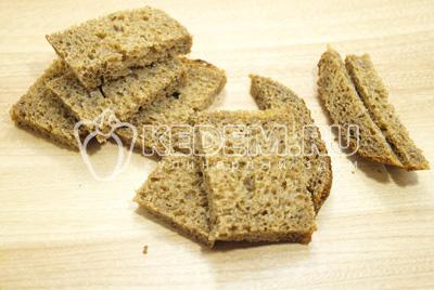 Срезать корочки со всех сторон и сделать небольшие прямоугольные кусочки хлеба