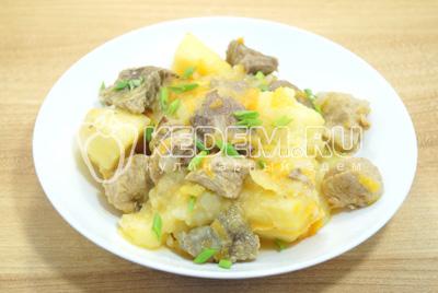 Тушеный картофель с мясом выложить на тарелки и поспать мелко нашинкованным зеленым луком.