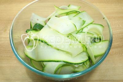 Настругать кабачки через терку или овоще чисткой тонкими пластами.