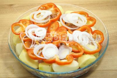 Выложить картофель на курицу, добавить с верху кружочками нарезанный перец и лук.