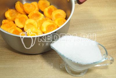 Выкладывать в кастрюлю для варки слоями, чередуя абрикосы с сахаром.