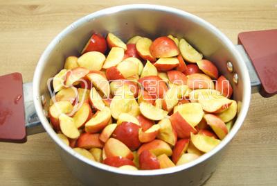 Разрезать на четвертинки и удалить сердцевину. Выложить яблоки в кастрюлю.