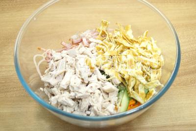 В миску с салатом добавить нашинкованные блинчики и куриное мясо.