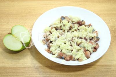 В салатник выложить нижним слоем селедку, затем натереть на терке очищенное яблоко.