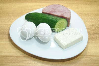 Яйца отварить, остудить и очистить, приготовить ветчину, огурец и сыр.