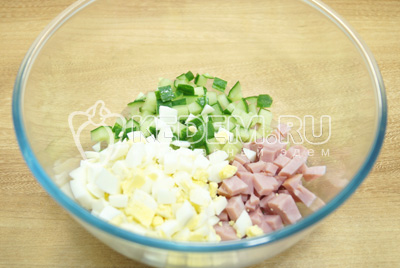 В миску нарезать кубиками огурец, ветчину и яйца.