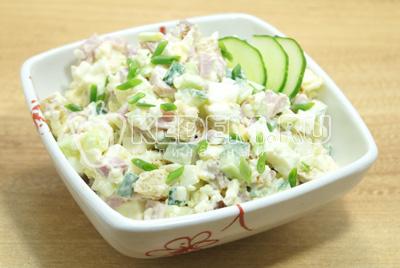 Готовый салат выложить в салатницу, украсить зеленым луком и ломтиками огурца.