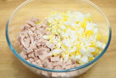 Нарезать кубиками в миску овощи. Добавить кубиками нарезанную вареную колбасу и яйца.