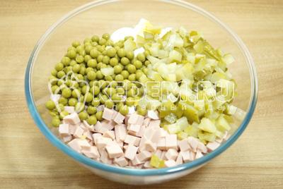 Добавить кубиками нарезанные маринованные огурцы и консервированный зеленый горошек.