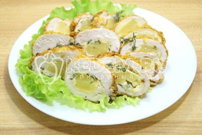 Нарезать ломтиками и выложить на блюдо с листьями салата.