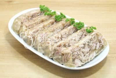 Готовый холодец выложить из формы. Разрезать на порционные кусочки. Выложить на блюдо. Украсить по желанию.
