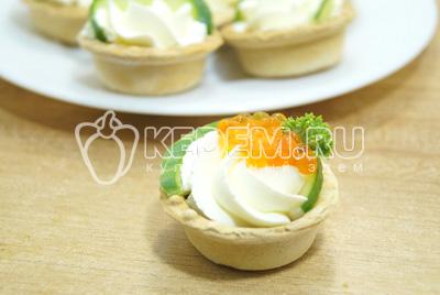 Выложить сверху  понемногу икры на каждую тарталетку и украсить зеленью петрушки.