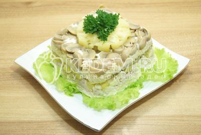 Перевернуть салат на блюдо с листьями салата и украсить сверху колечком ананаса и зеленью.