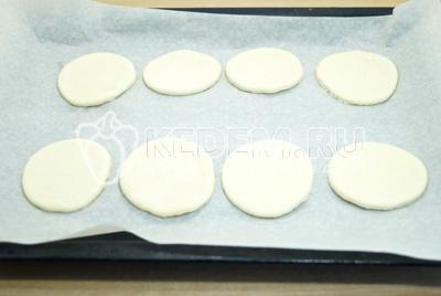Вырезать формочкой кружочки и выложить на противень застеленный пергаментов. Смазать в сбитым яйцом.