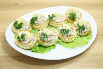 Выложить на блюдо с листьями салата, украсить зеленью и дольками лимона.
