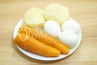 Картофель, морковь и яйца отварить, отсудить и очистить.