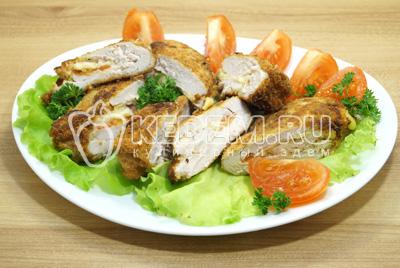 Разрезать на ломтики и выложить на блюдо с зеленью.
