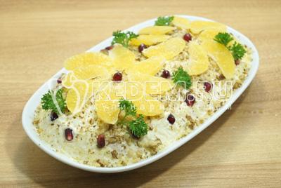 Посыпать измельченными орехами и украсить дольками мандарина и зеленью.