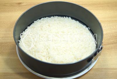 В сервировочное кольцо или разъемную форму для выпечки выложить первый слой отварного риса.