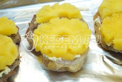 Смазать немного майонезом и выложить колечки ананаса.