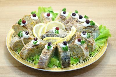 Запекать в  духовке 30 минут, при 180 градусах С. Готовую рыбу остудить и нарезать ломтиками, выложить на блюдо с листьями салата и украсить ягодами клюквы и ломтиками лимона.
