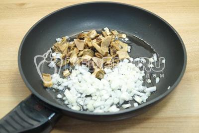 На сковороде  с растительным маслом, обжарить мелко нашинкованный лук и нарезанные размоченные грибы.