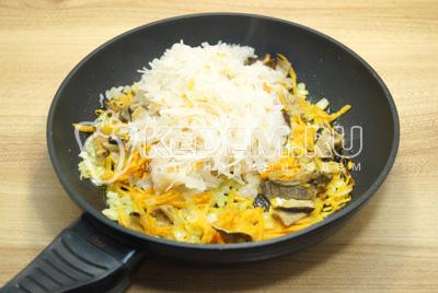 Добавить квашеную капусту и нарезанные грибы и готовить еще 3-4 минуты.