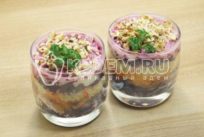 Добавить слой мелко покрошенных грецких орехов и зелень.