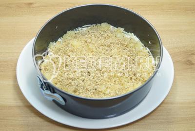 Добавить слой половины измельченных грецких орехов.