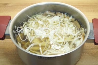 В кастрюлю с грибами сложить картофель и нашинкованную капусту. Варить 10-12 минут.