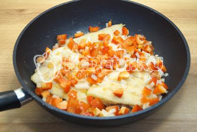 В сковороду к рыбе добавить кубиками нарезанный лук и болгарский перец.