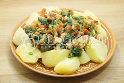 Выложить на блюдо картофель сверху выложить мясо с зеленью.