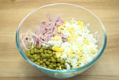 Нарезать в миску яйца, колбасу и добавить консервированный горошек.
