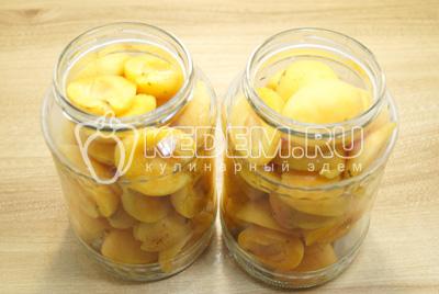 Разделить на половинки и удалить косточки. Заполнить чистые банки половинками абрикосов до верха.