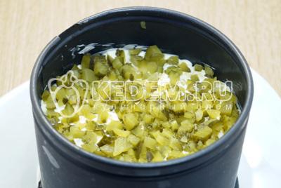 Хорошо смазать слой сыра майонезом и выложить слой мелко нарезанных маринованных огурцов.
