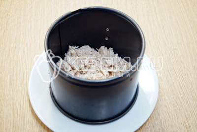 В сервировочное кольцо выложить слой мелко нарезанной курицы. Смазать майонезом.
