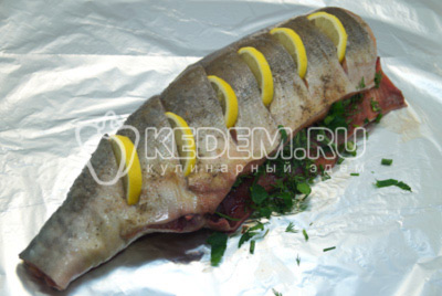 Сделать нарезы и вложить ломтики лимона. Начинить рыбу нашинкованной зеленью. Выложить на фольгу.