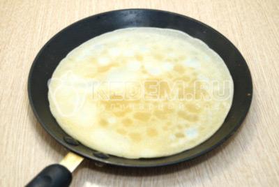 Разогреть блинную сковороду и выпекать тонкие блинчики с двух сторон.