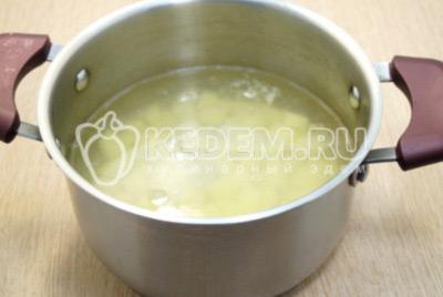 В кастрюлю налить воду и добавить картофель, поставить варить.