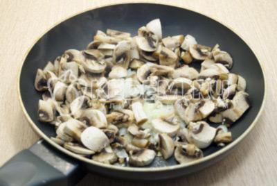 Лук мелко нашинковать, грибы нарезать и обжарить на сковороде с растительным маслом 3-5 минут, помешивая.