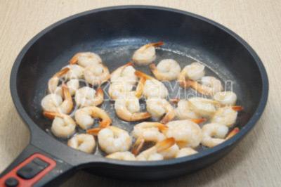 Разогреть оливковое масло на сковороде и обжарить креветки 5-6 минут, помешивая. Снять креветки со сковороды.